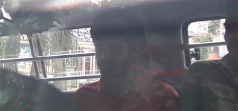 Screengrab from fuzzy  Channel NewsAsia video news of deportees in police van